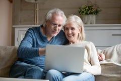 Lyckliga åldriga par kopplar av på soffan genom att använda bärbara datorn tillsammans fotografering för bildbyråer