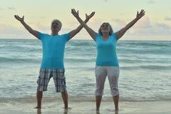 Lyckliga åldringpar som vilar på den tropiska stranden Arkivbild