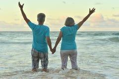 Lyckliga åldringpar som vilar på den tropiska stranden Royaltyfria Bilder