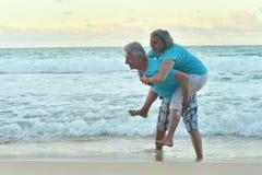 Lyckliga åldringpar som vilar på stranden Arkivbilder