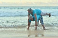 Lyckliga åldringpar som vilar på stranden Royaltyfria Foton