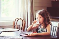 Lyckliga 8 år gammal barnflicka som har frukosten i landskök och att dricka mjölkar och äta rostat bröd Fotografering för Bildbyråer