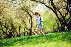 Lyckliga 3 år gammal barnpojke som fångar fjärilar med netto på gå i solig trädgård eller, parkerar Utomhus- activitie för vår oc arkivfoto