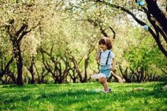 Lyckliga 3 år gammal barnpojke som fångar fjärilar med netto på gå i solig trädgård eller, parkerar Utomhus- activitie för vår oc arkivbild
