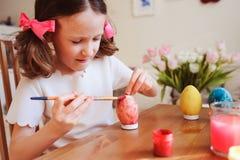 Lyckliga 7 år gammal ungeflicka som målar easter ägg Påskhantverk- och ferieförberedelser Arkivfoton