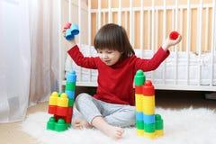 Lyckliga 2 år litet barn som spelar plast- kvarter Arkivfoto