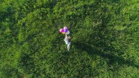 Lyckliga ögonblick surrsikt av tonårigt med kulöra ballonger rotera på bakgrund av gräs stock video