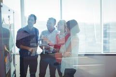 Lyckliga affärsentreprenörer som ser whiteboarden som ses till och med exponeringsglas royaltyfria foton