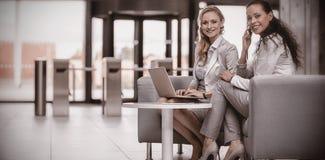 Lyckliga affärskvinnor som använder bärbara datorn och talar på mobiltelefonen royaltyfri fotografi
