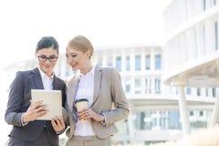Lyckliga affärskvinnor som använder den digitala minnestavlan utanför kontorsbyggnad arkivfoto