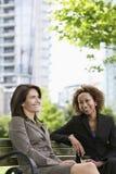 Lyckliga affärskvinnor som sitter på, parkerar bänken Royaltyfri Foto
