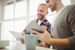Lyckliga affärsmän som i regeringsställning använder den digitala minnestavlan Arkivbilder