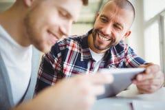 Lyckliga affärsmän som i regeringsställning använder den digitala minnestavlan Arkivfoton