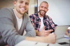 Lyckliga affärsmän som i regeringsställning använder den digitala minnestavlan på skrivbordet Royaltyfria Foton