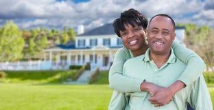 Lyckliga afrikansk amerikanpar framme av det härliga huset Royaltyfri Foto