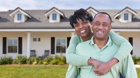 Lyckliga afrikansk amerikanpar framme av det härliga huset Royaltyfri Bild