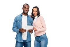 lyckliga afrikansk amerikanpar genom att använda den digitala minnestavlan och le på kameran Royaltyfria Foton