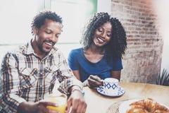 Lyckliga afrikansk amerikanpar har frukosten tillsammans i morgonen på trätabellen Le svarta mannen och hans Royaltyfri Foto