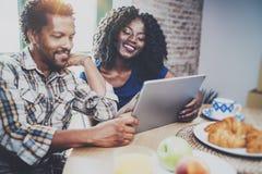 Lyckliga afrikansk amerikanpar har frukosten tillsammans i morgonen på trätabellen Le svarta mannen och hans Royaltyfria Bilder