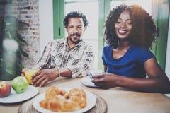 Lyckliga afrikansk amerikanpar har frukosten tillsammans i morgonen på trätabellen Le svarta mannen och hans Arkivfoto