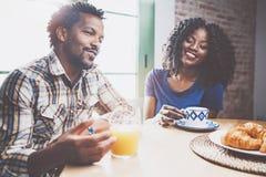 Lyckliga afrikansk amerikanpar har frukosten tillsammans i morgonen på trätabellen Ung svart man och hans Arkivfoto