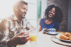 Lyckliga afrikansk amerikanpar har frukosten tillsammans i morgonen på trätabellen Ung svart man och hans Royaltyfria Bilder