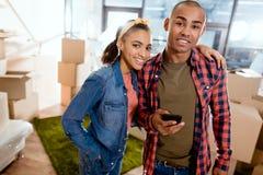 lyckliga afrikansk amerikanpar med smartphonen Fotografering för Bildbyråer