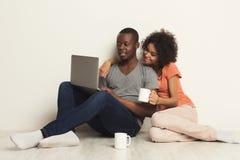 Lyckliga afrikansk amerikanpar som direktanslutet shoppar royaltyfria foton