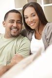 Lyckliga afrikansk amerikanpar som hemma sitter Arkivfoton
