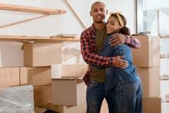 lyckliga afrikansk amerikanpar som kramar i ny lägenhet Arkivbild