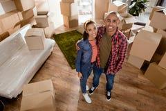 lyckliga afrikansk amerikanpar som kramar i nytt hem Fotografering för Bildbyråer
