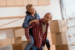 lyckliga afrikansk amerikanpar som piggybacking i ny lägenhet Arkivbilder