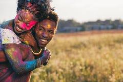 Lyckliga afrikansk amerikanpar som piggybacking på holifestivalen Royaltyfri Foto