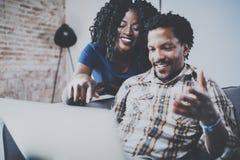 Lyckliga afrikansk amerikanpar som tillsammans kopplar av på soffan Ung svart man och flicka som använder den moderna bärbara dat Fotografering för Bildbyråer