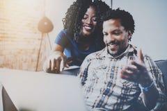 Lyckliga afrikansk amerikanpar som tillsammans kopplar av på soffan Ung svart man och flicka som använder den moderna bärbara dat Arkivfoton