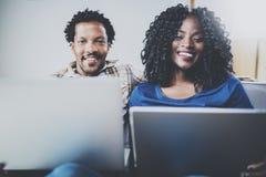 Lyckliga afrikansk amerikanpar som tillsammans kopplar av på soffan Ung svart man och flicka som hemma använder moderna antecknin Arkivbild
