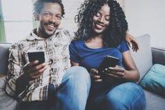 Lyckliga afrikansk amerikanpar som tillsammans kopplar av på soffan Ung svart man och hans flickvän som använder mobiltelefoner m Royaltyfri Fotografi