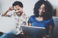 Lyckliga afrikansk amerikanpar som tillsammans kopplar av på soffan Ung svart man och hans flickvän som använder moderna bärbara  Arkivfoton