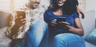 Lyckliga afrikansk amerikanpar som tillsammans kopplar av på soffan Ung svart man och hans flickvän som använder smartphones meda Royaltyfri Fotografi