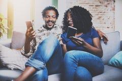 Lyckliga afrikansk amerikanpar som tillsammans kopplar av på soffan Ung svart man och hans flickvän som använder smartphones meda Royaltyfri Foto