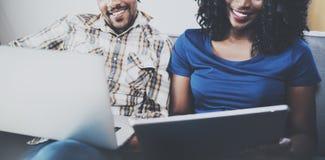 Lyckliga afrikansk amerikanpar som tillsammans kopplar av på soffan Ung svart man och hans flickvän som hemma använder bärbara da Royaltyfria Bilder