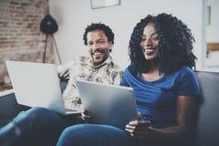 Lyckliga afrikansk amerikanpar som tillsammans kopplar av på soffan Ung svart man och hans flickvän som hemma använder bärbara da Royaltyfria Foton