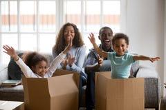 Lyckliga afrikanska föräldrar och ungar som spelar i askar, tycker om förflyttning arkivfoton