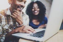 Lyckliga afrikanska par som har, vilar på ett hem: svart mansammanträde på tabellen, genom att använda bärbara datorn och att skr royaltyfri bild