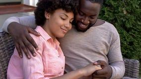 Lyckliga afrikanska par som kramar på bänken, utomhus- datum i stadskafé, closeness royaltyfri foto