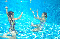 Lyckliga aktiva ungar simmar i pöl och spelar undervattens- Royaltyfri Foto