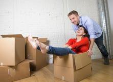 Lyckliga amerikanska par som packar upp det nya huset för inflyttning som spelar med packade upp kartonger Fotografering för Bildbyråer