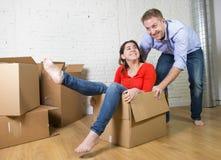 Lyckliga amerikanska par som packar upp det nya huset för inflyttning som spelar med packade upp kartonger Royaltyfri Fotografi