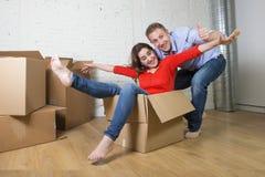 Lyckliga amerikanska par som packar upp det nya huset för inflyttning som spelar med packade upp kartonger Arkivbild