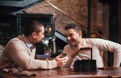 Lyckliga angenäma män som till varandra talar Fotografering för Bildbyråer